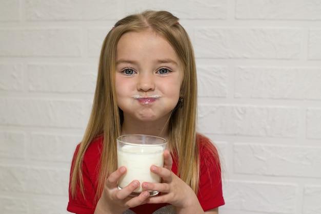Wesołe dziecko trzyma szklankę mleka