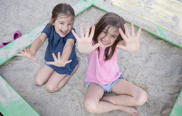 Wesołe dziewczynki siedzą w piaskownicy i bawią się piaskiem w upalny letni dzień.