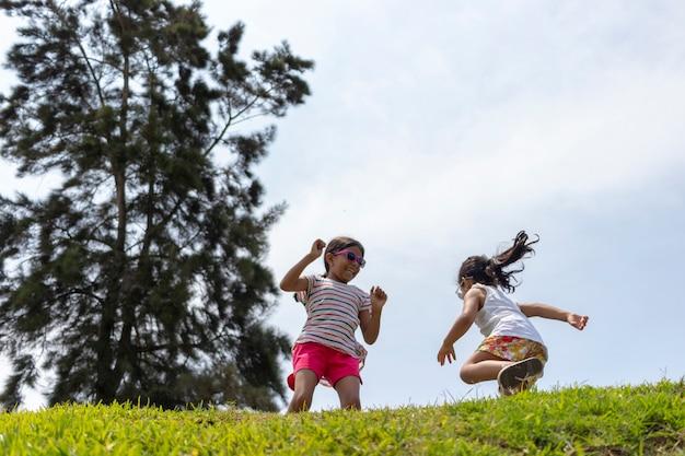 Wesołe dziewczyny, bawiące się razem w parku