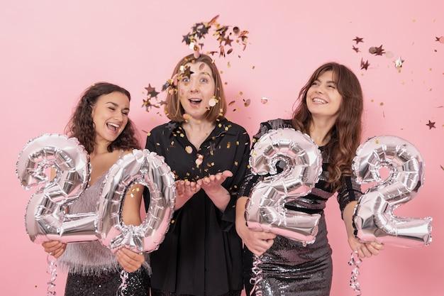 Wesołe dziewczyny na różowym tle wśród konfetti trzymają srebrne balony foliowe z cyframi 2022, sylwestrowa zabawa.