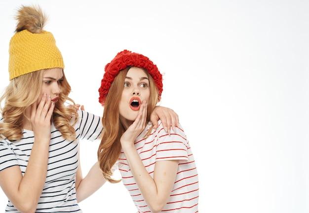 Wesołe dziewczyny w czapkach przytulają się