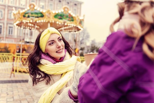 Wesołe emocje. piękna brunetka czuje szczęście patrząc na córkę