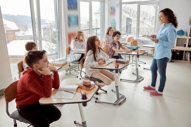 Wesołe i szczęśliwe dzieci siedzą przy biurku, podczas gdy nauczyciel mówi w klasie szkolnej. dzieci ze szkoły podstawowej siedzą na biurkach.