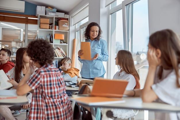 Wesołe i szczęśliwe dzieci siedzą przy biurku, podczas gdy nauczyciel mówi w klasie szkolnej.