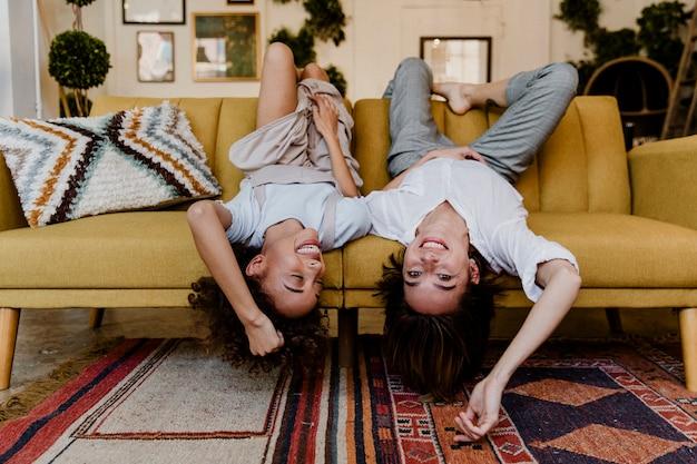 Wesołe kobiety leżące do góry nogami na musztardowożółtej kanapie