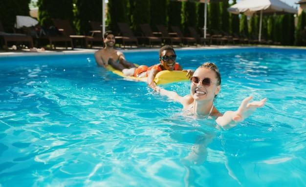 Wesołe koleżanki pływają na materacu w basenie. szczęśliwi ludzie bawią się na letnie wakacje, impreza świąteczna przy basenie na świeżym powietrzu. jeden mężczyzna i dwie kobiety wypoczywają w ośrodku?