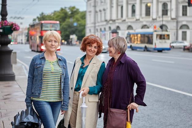Wesołe koleżanki w średnim wieku stoją na ulicy miasta w sankt petersburgu w rosji.