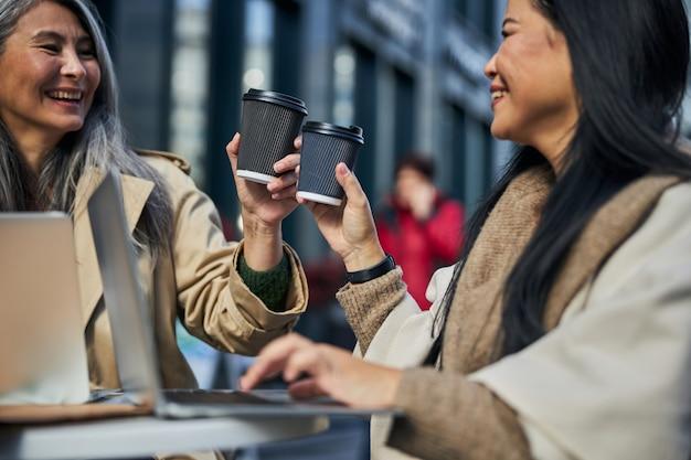 Wesołe koleżanki wznoszące tosty z kawą w kawiarni na świeżym powietrzu
