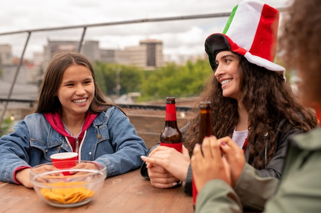 Wesołe ładne dziewczyny z drinkami siedzą przy stole po meczu piłki nożnej i rozmawiają o swojej ulubionej drużynie