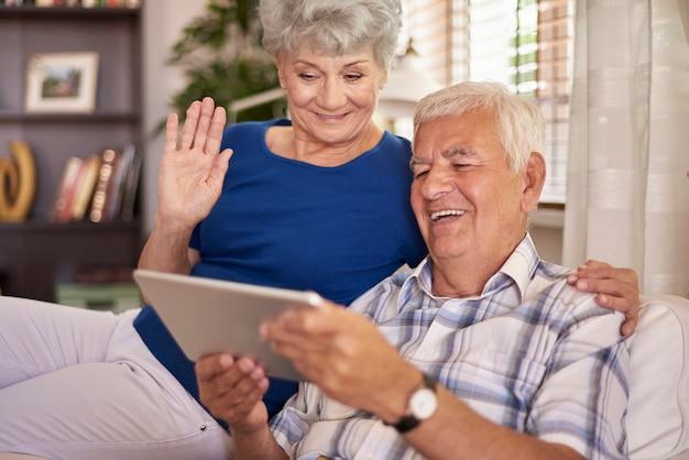 Wesołe małżeństwo seniorów za pomocą cyfrowego tabletu