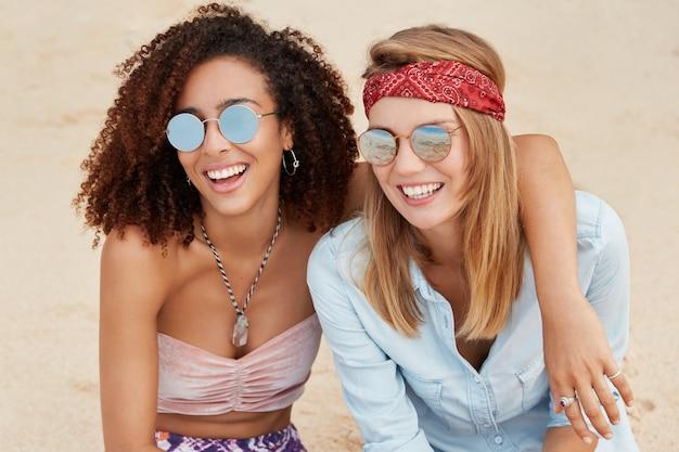 Wesołe młode kobiety przytulają się na plaży, pozytywnie patrzą w dal, bawią się razem podczas letniego kurortu. afroamerykanka i jej dziewczyna mają randkę na świeżym powietrzu w pobliżu morza lub oceanu