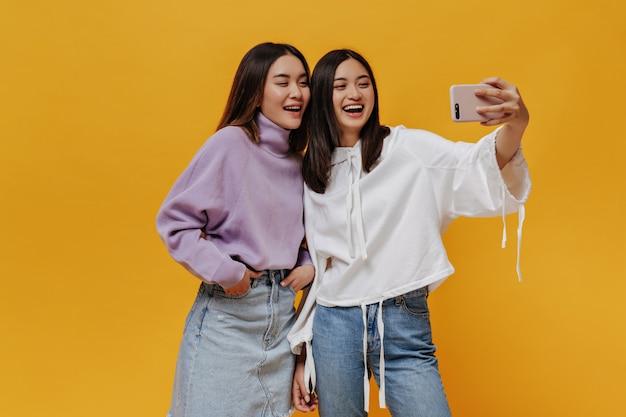Wesołe młode kobiety w dżinsowych strojach uśmiechają się na białym tle