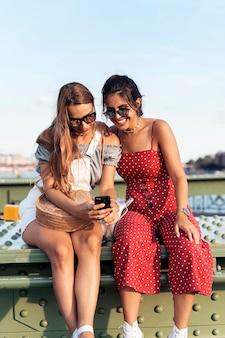Wesołe młode kobiety w okularach przeciwsłonecznych, siedząc na moście i surfując po internecie na telefonie komórkowym miasta