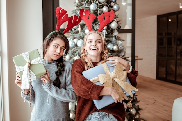 Wesołe młode panie z niezwykłymi fryzurami przytulające pudełka na prezenty i będące w doskonałym nastroju na świąteczną koncepcję bożego narodzenia