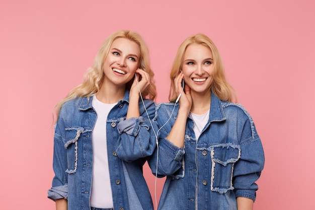 Wesołe młode piękne blondynki z falującymi fryzurami uśmiechają się radośnie, słuchając muzyki w heaphones, stojąc na różowym tle