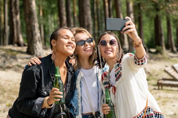Wesołe młode wieloetniczne kobiety pozujące z piwem do selfie podczas spędzania czasu w leśnym obozie