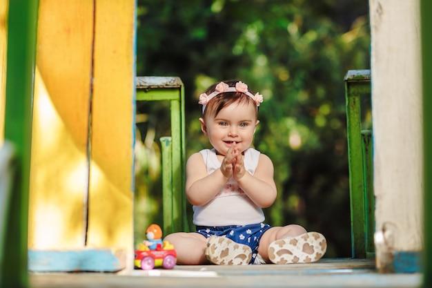 Wesołe ośmiomiesięczne dziecko na placu zabaw klaszcze w dłonie i śmiejąc się