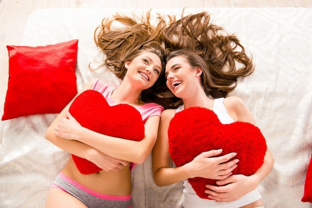 Wesołe piękne dziewczyny w piżamie śmiejące się i leżące na łóżku trzymając poduszki