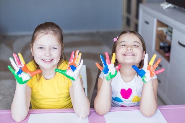 Wesołe radosne dziewczyny rasy kaukaskiej bawiące się wraz z kolorowymi farbami. malowane dziewczyny palce. rysowanie w domu. gry i rozrywka dla dzieci podczas wakacji lub kwarantanny