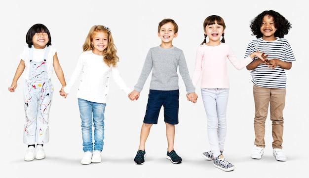 Wesołe, różnorodne dzieci trzymające się za ręce
