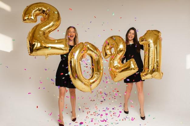 Wesołe siostry rasy kaukaskiej trzymają duże złote balony z numerami 2021, zdjęcie na białej ścianie