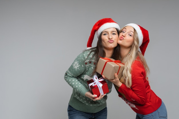 Wesołe siostry rasy kaukaskiej w ciepłych zielonych i czerwonych swetrach trzymają prezenty świąteczne, zdjęcie na białej ścianie
