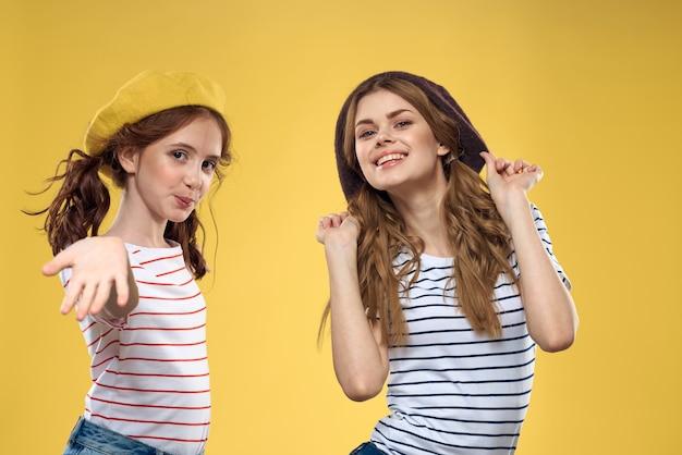 Wesołe siostry w czapkach koszulki w paski radość styl życia żółte tło rodzina