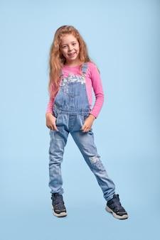 Wesołe słodkie dziecko w dżinsowych kombinezonach i modnych trampkach stojących z rękami w kieszeniach