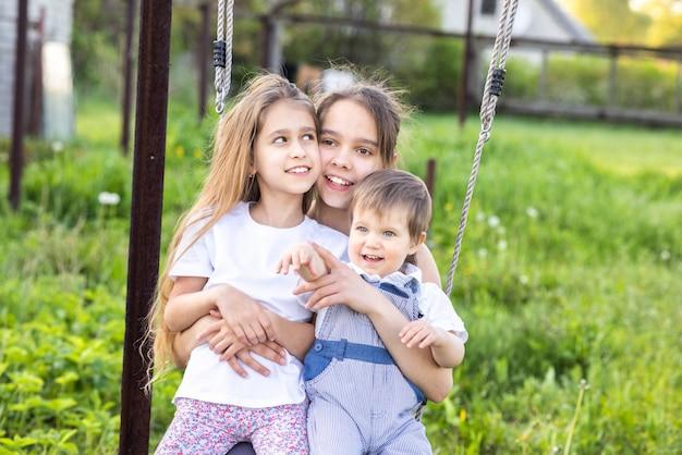 Wesołe szczęśliwe dwie siostry i maluch brat w lekkich wiosennych ubraniach. baw się dobrze, jedź na ulicznej czerwonej huśtawce w domu kwitnącym zielonym ogrodzie i śmiej się z szerokim uśmiechem