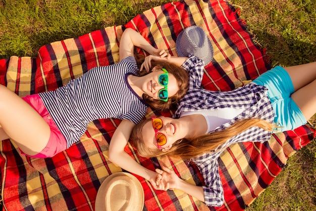 Wesołe szczęśliwe kobiety piknik w parku i leżące na kratę