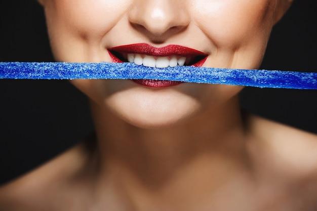 Wesołe usta trzymając cukierki zębami.