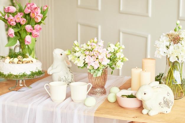 Wesołego alleluja! dekoracje świąteczne. piękny świąteczny stół wielkanocny z króliczkiem, kwiatami i jajkami. motyw kolor wiosny, miejsce. szablon wielkanocny kartkę z życzeniami. wnętrza kuchenne.