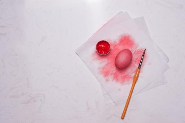 Wesołego alleluja! malowanie czerwonych pisanek na stole.