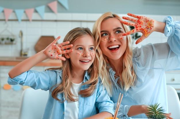 Wesołego alleluja! mama i córka bawią się pokazując ręce na aparacie poplamione kolorowymi wielkanocnymi cukierkami, podczas gdy malują jajka przygotowując się do świąt.