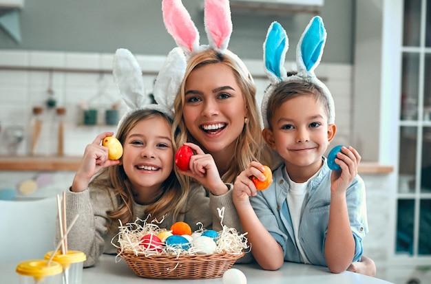 Wesołego alleluja! matka, syn i córka zaczynają polować na pisanki. szczęśliwa rodzina przygotowuje się do wielkanocy. ładny mały chłopiec i dziewczynka sobie uszy królika na wielkanoc.