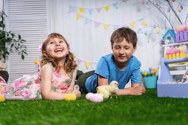 Wesołego alleluja! śliczni roześmiani dzieci kłamają na trawie z jajkami i małymi kurczakami.