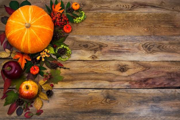 Wesołego dziękczynienia wystrój z dynią, jabłkami i jesiennymi liśćmi po lewej stronie rustykalnego drewnianego stołu. jesienne tło z sezonowymi warzywami i owocami, kopia przestrzeń