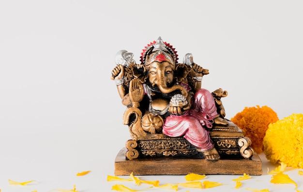Wesołego festiwalu ganesh chaturthi z posągiem lorda ganesha i kwiatami