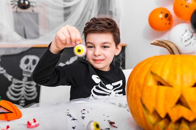 Wesołego halloween! atrakcyjny młody chłopak w kostiumie bawi się i bawi się przerażającą dekoracją oczu