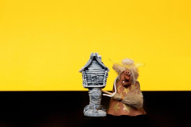 Wesołego halloween. baba jaga z chatą na udkach z kurczaka na żółtym tle. pojedyncze miejsce na twój tekst.