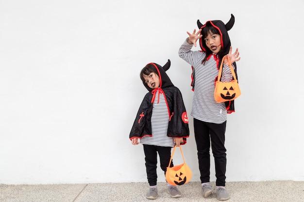 Wesołego halloween! dwoje dzieci w kostiumach na halloween i z dyniami na białym tle
