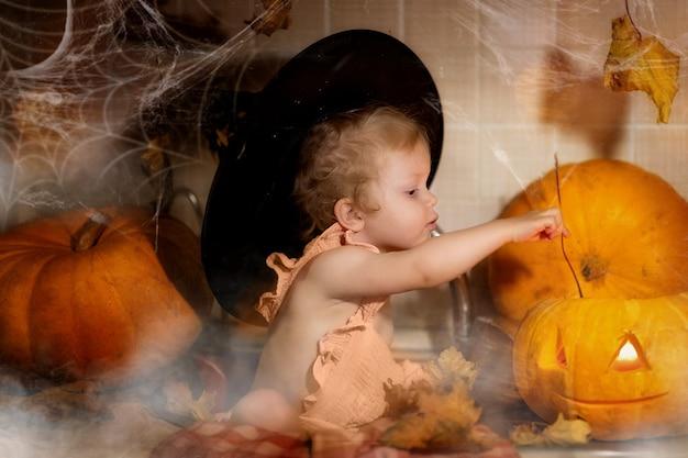 Wesołego halloween. dziewczyna w kapeluszu czarownic i garniturze trzyma dynię.
