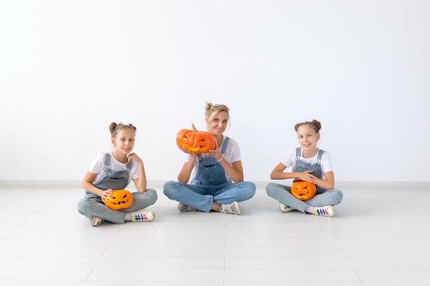Wesołego halloween i święta koncepcja - matka i jej córki z dyni. szczęśliwa rodzina