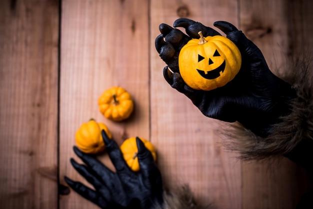 Wesołego halloween. ręce wilkołaka lub zombie malują straszną dynię na imprezę cukierek albo psikus. skopiuj miejsce na tekst