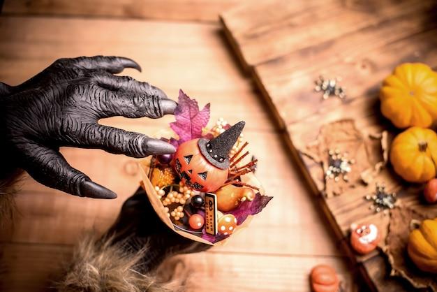 Wesołego halloween. ręce wilkołaka lub zombie robiące przerażający prezent z dyni na imprezę cukierek albo psikus. skopiuj miejsce na tekst