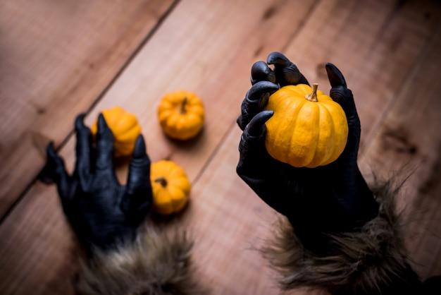 Wesołego halloween. ręce wilkołaka lub zombie trzymające dynię na imprezę cukierek albo psikus.