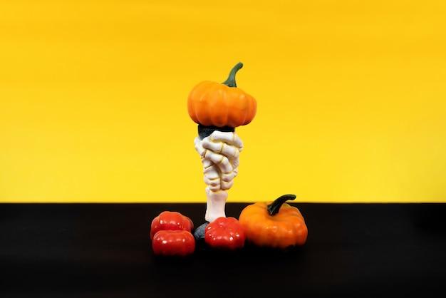 Wesołego halloween. ręka wiedźmy z wieloma różnymi dyniami na żółtym i czarnym tle