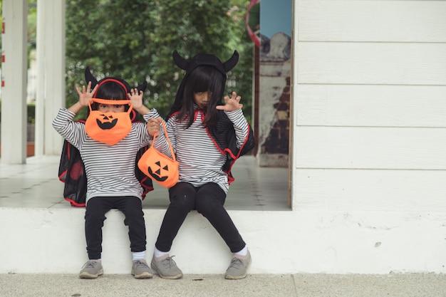Wesołego halloween. rodzeństwo dziewczyna w garniturach i z dyniami w domu