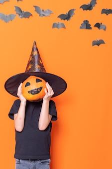 Wesołego halloween. straszne dzieci halloween. chłopiec w kapeluszu trzymający dynię przed głową na pomarańczowym tle z papierowymi nietoperzami, pionowa ramka. koncepcja halloween cukierek albo psikus.