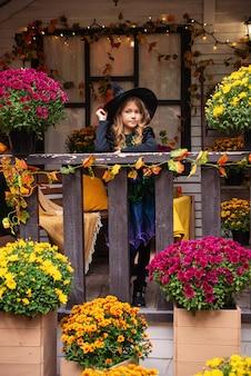 Wesołego halloween urocza śmiejąca się mała dziewczynka w strojach wiedźmy świętuje halloween